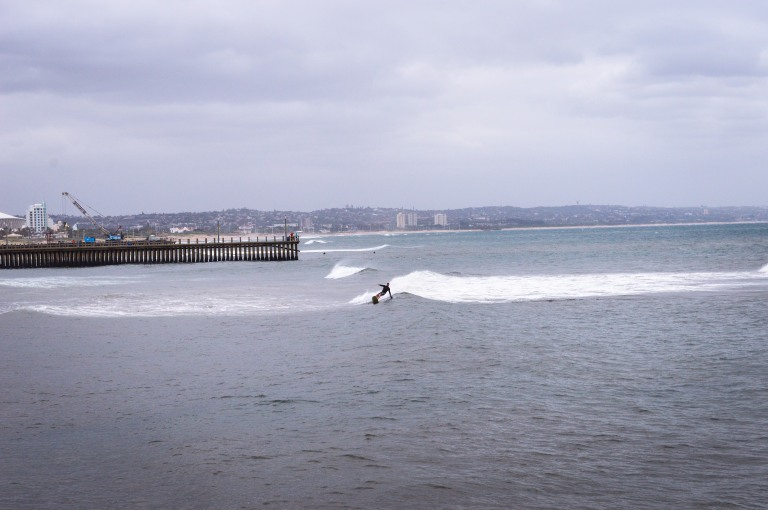 Surfer catching a wave on the beach in Durban 2015