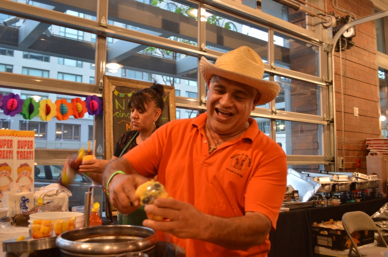 Nieve Cinco de Mayo owner Luis Abundis serving ice cream to attendees